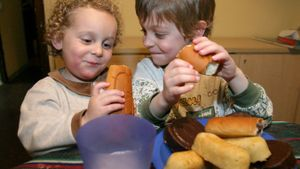 Dos niños comiendo bollería.