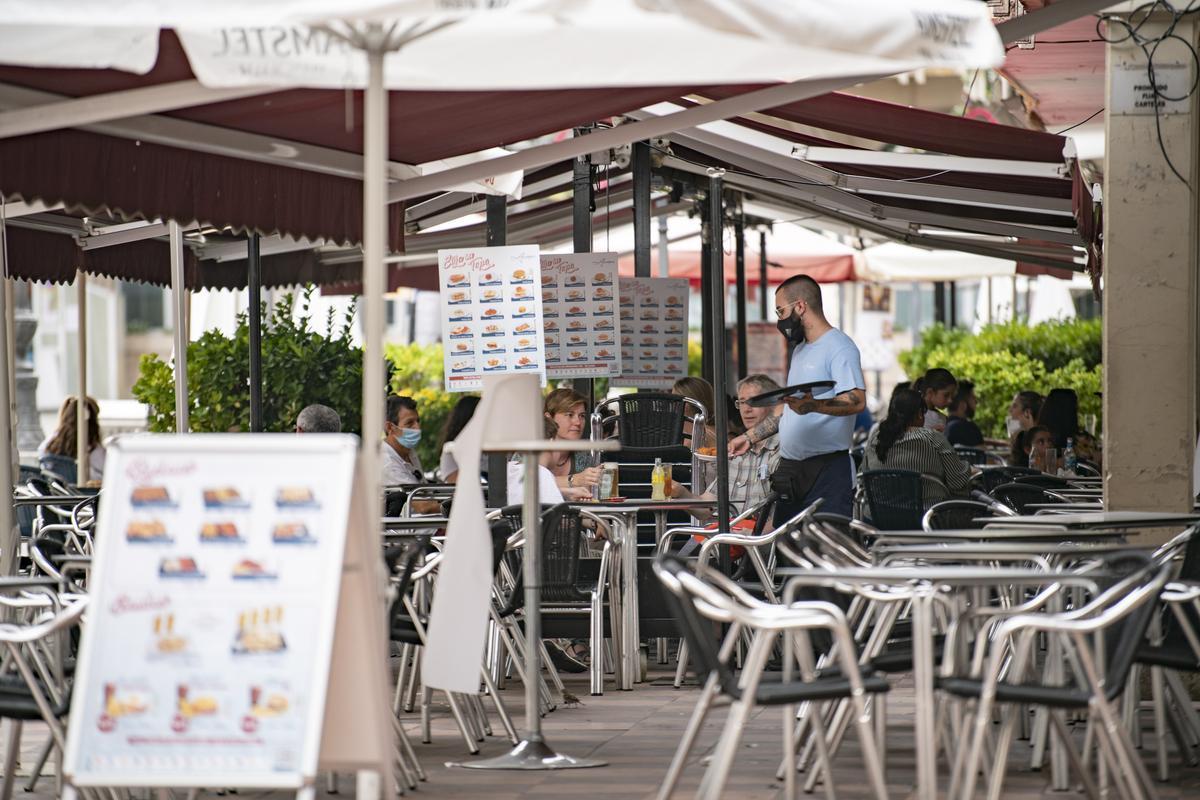 Un camarero atiende una mesa en la terraza de una cafetería